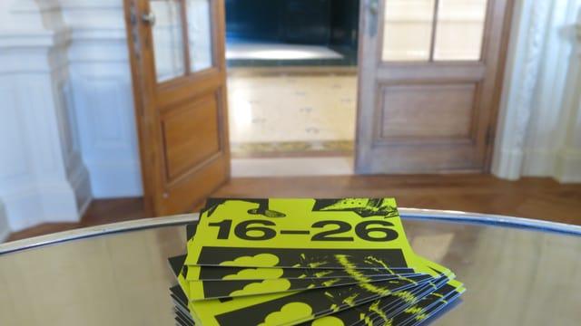 Kreditkartengrosse, gelbe Jugendkulturpässe liegen auf einem Tisch im Berner Stadttheater.