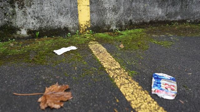 Eine zerdrückte Bierdose rechts im Bild, in der Mitte ein gelber Streifen der Parkplatz-Markierung. Darüber Moos und ein braunes Blatt.