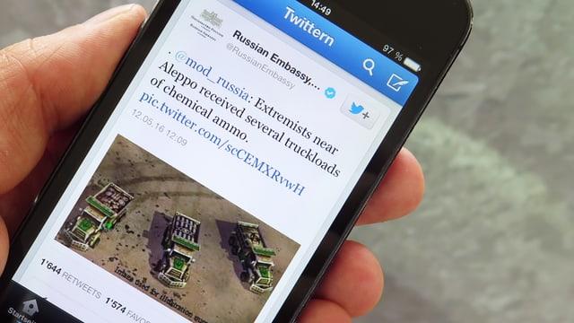 Auf einem Handy ist ein Tweet zu sehen mit einem Bild, auf dem drei Lastwagen abgebildet sind.