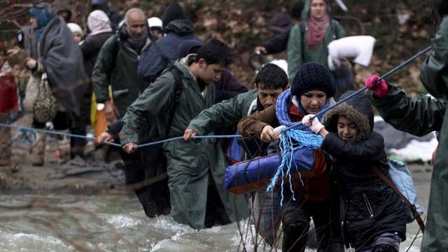 Flüchtlinge durchqueren einen Fluss und halten sich an einem Seil.