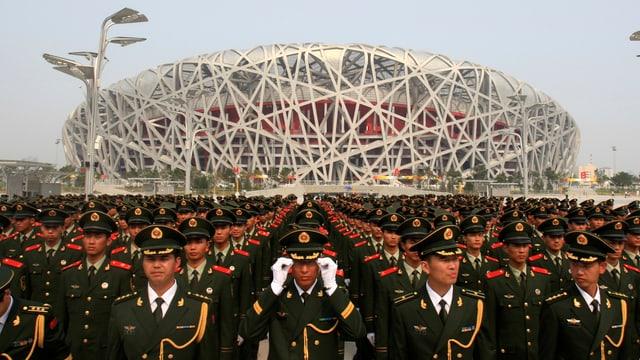 Eine Aussenaufnahme des Stadions in Peking, davor eine Militärparade.