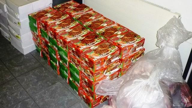 Säcke mit rohem Fleisch und Schachteln mit vorgefertigten Burgern im Lagerraum der Grenzwache