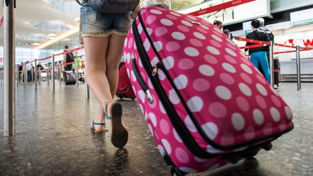 Eine junge Frau zieht einen am Flughafen einen Koffer mit Punkten hinter sich her.