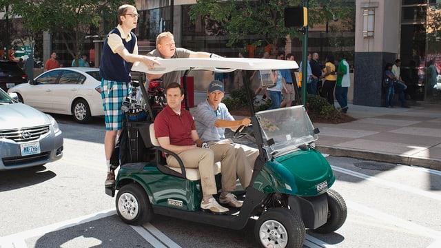Vier Männer fahren auf einem Golfmobil umher.