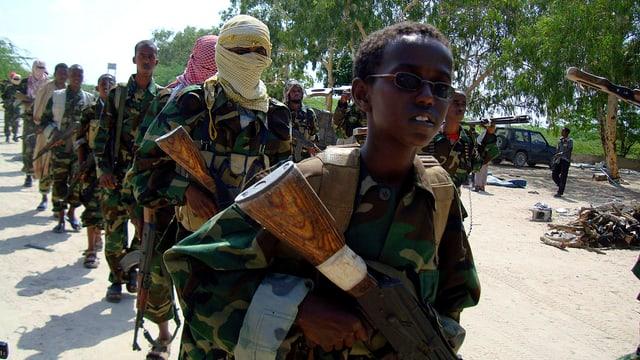 Kindersoldat in Uniform mit Gewehr. im Hintergrund marschieren weitere junge Soldaten.