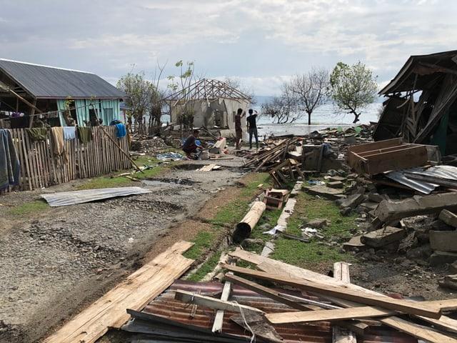 Zerstörte Häuser, dahinter das Meer