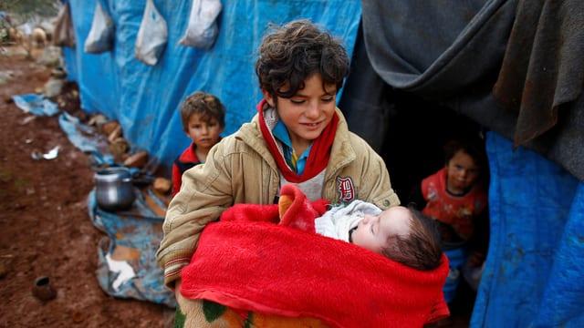 Ein Knabe hält ein Baby vor einem Zelt.