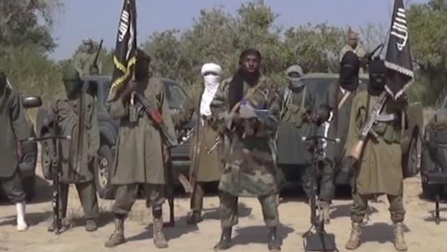 Gruppe von maskierten Boko-Haram-Mitgliedern vor ihren Trucks