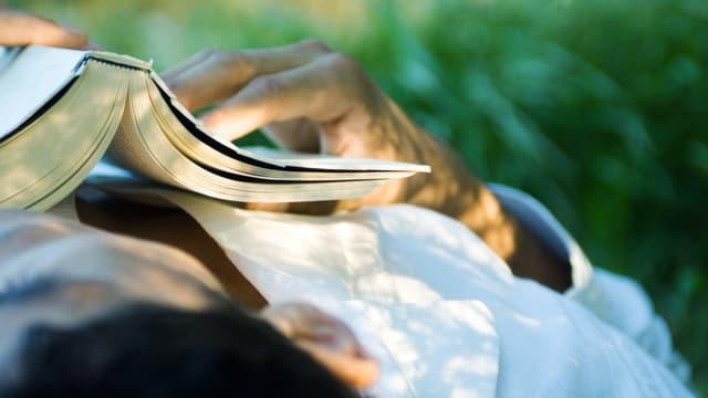 Ein Mann liest auf einer Wiese. Er hat ein Buch auf der Brust.
