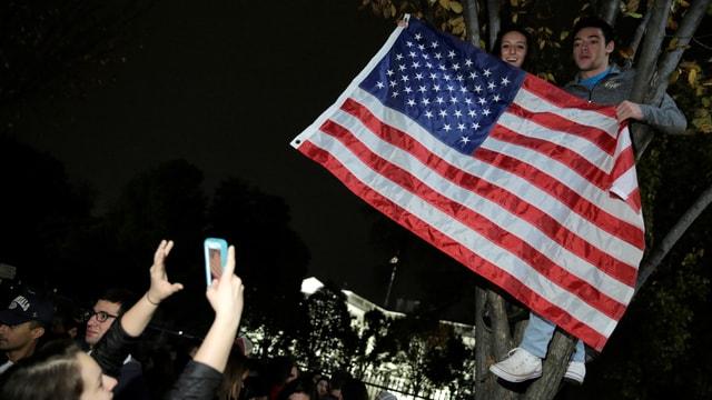 Junge Menschen in einem Baum vor dem Weissen Haus mit einer US-Flagge.