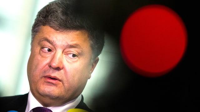 Der pro-westliche ukrainische Präsident Petro Poroschenko st6eht im Gegenlicht einer roten Lampe.