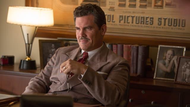 Eddie Mannix sitzt an seinem Schreibtisch.