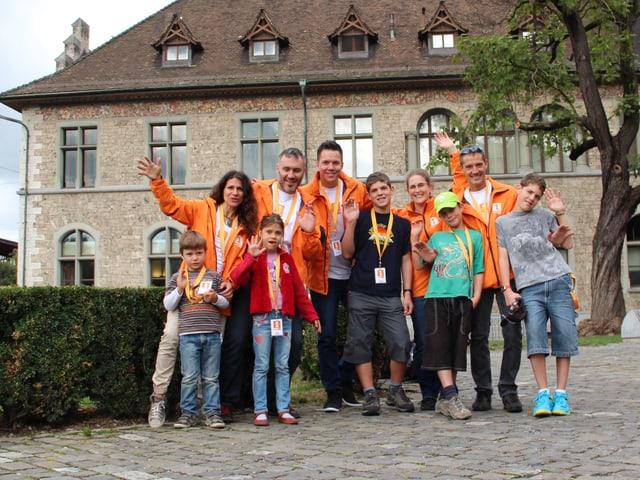 Das Gruppenfoto zeigt die beiden Familien und Sven Epiney in orangen Jacke im Freien vor dem Landesmuseum.