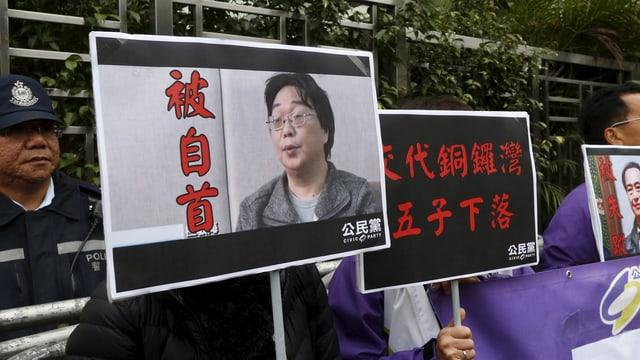 Ein Demonstrant hält ein Schild mit einem Bild von Gui Minhai.