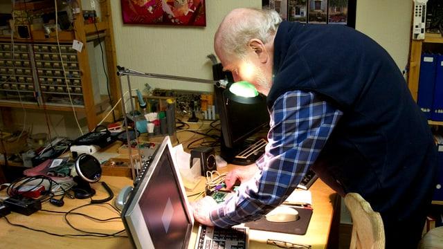 Niklaus Wirth bastelt in seiner Werkstatt an einer Platine herum.