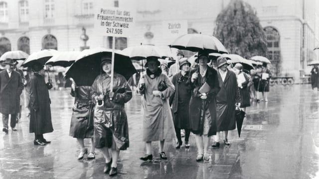eine schwarz-weiss Fotografie von Frauen mit einem Plakat und Regenschirmen