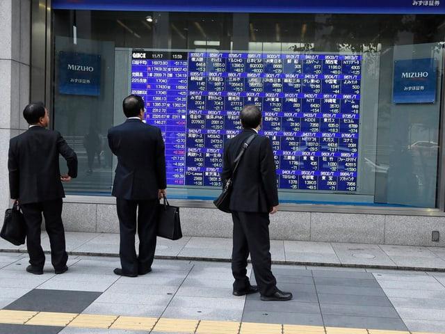 Japanische Gschäftsleute vor Bildschirmen mit Börsenkursen.