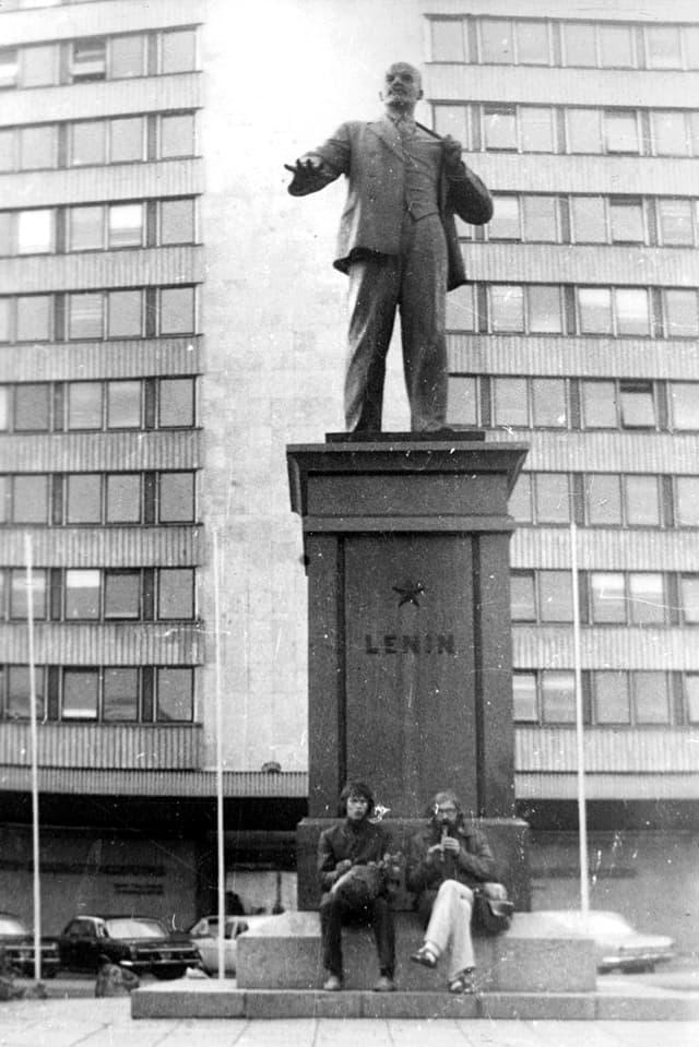 Altes Foto: Zwei Männer sitzen vor dem Sockel einer Lenin-Statue. Einer Spielt Blockflöte.