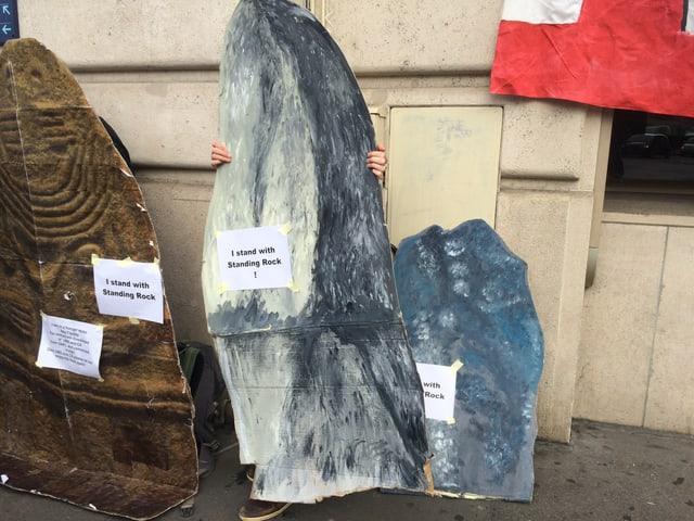 """Gebastelte Steine mit Aufschriften wie """"I stand with Standing Rock""""."""