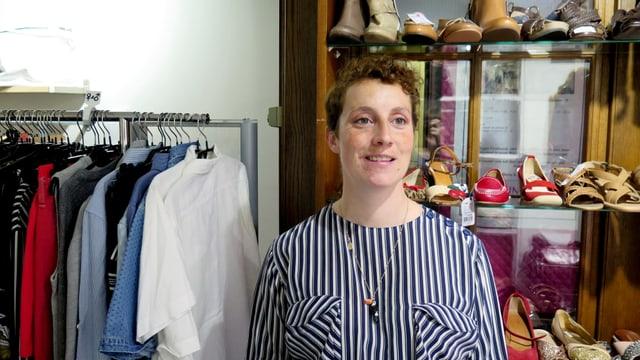 Eine Frau vor Kleiderstangen.