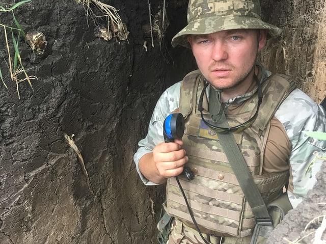 Ein junger Mann in Soldaten-Kluft steht in einer Art Schützengraben udn hält einen Telefonhörer in der Hand.