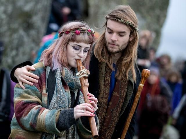 Junge Frau spielt Flöte, junger Mann hält Arm um sie