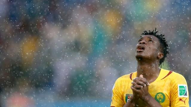 Brasilianischer Nationalfussballer betet mit Blick zum Himmel in strömendem Regen.