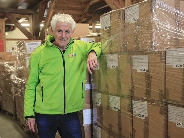 Florenz Schaffner steht, angelehnt an einen grossen Stapel Kartonkisten, in einer Lagerhalle.