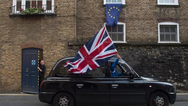 In auto cun ina bandiera da la Gronda Britannia avant ina chasa cun ina bandiera da l'UE.