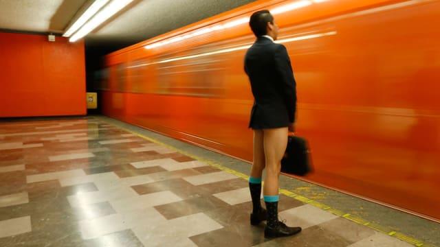 Mann in Anzug ohne Hose steht vor einer vorbeifahrenden U-Bahn in Mexico-City.
