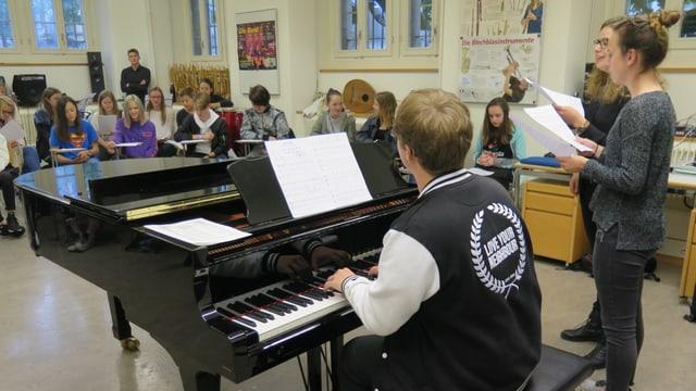 Ein Studierender spielt am Piano, Schüler singen dazu.