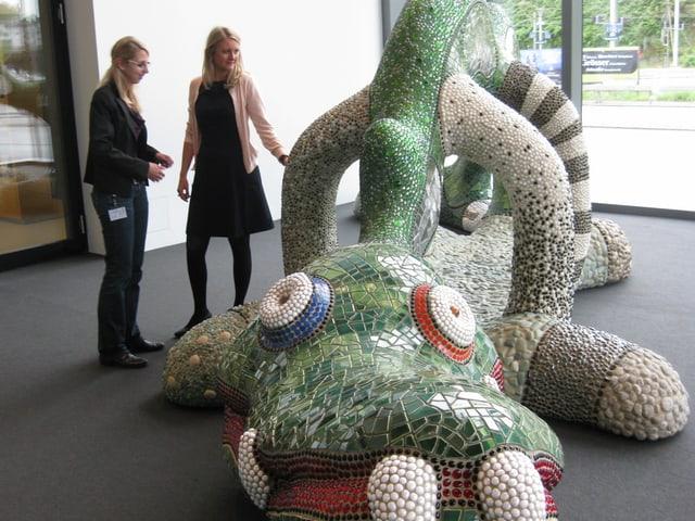 Zwei Frauen vor einer Skulptur.