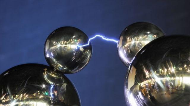 Ein Blitz verbindet zwei silberne Kugeln vor blauem Hintergrund.