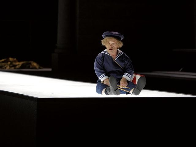 Mann in Matrosenküstum, Schlagzeugschlägern und Trommel sitzt auf einem hell, von unten beschienen Bühnenteil.