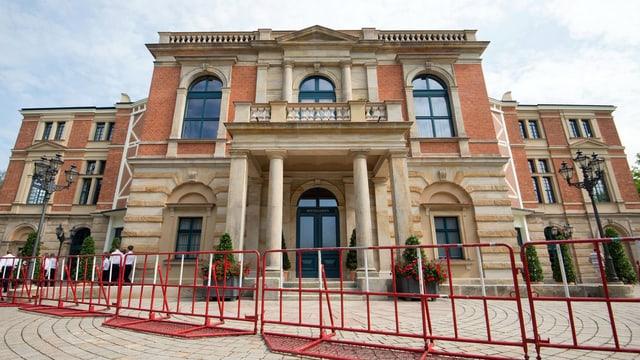 Das kalssizistische Bayreuther Festspielhaus, vor dem rote Abschrankungen auffgebaut sind.