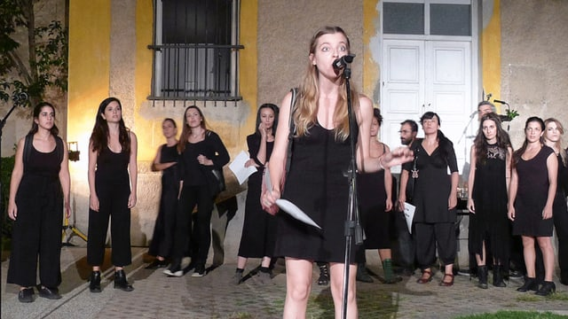 Eine Frau am Mikrofon. Hinter ihr stehen mehrere Frauen.
