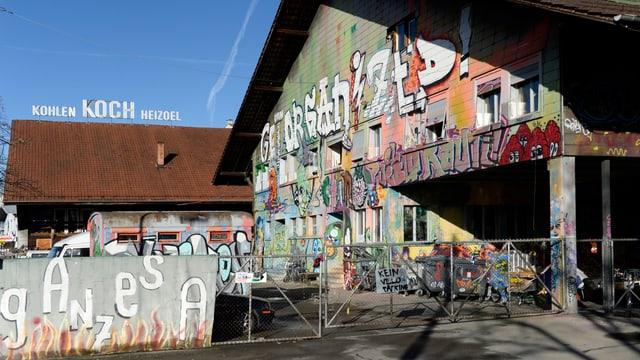 Fassaden und Mauern mit Sprayereien. Auf dem Dach der Schriftzug Wärme - Koch - Heizöl