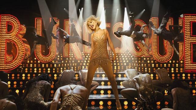 Eine Frau tanzt und singt auf eine Bühne. Sie ist umgeben von anderen Tänzerinnen. Im Hintergrund ist die Leuchtschrift «Burlesque» zu sehen.