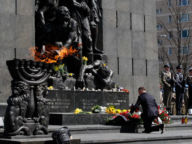 Eine Person kniet vor dem Sockel eines Denkmals.