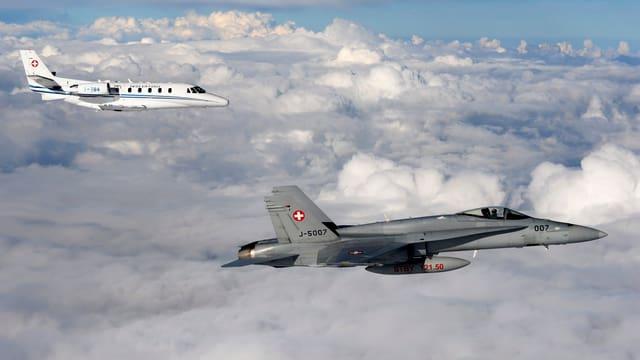 Ein F/A-18-Kampfjet begleitet den Bundesratsjet hoch über den Wolken.