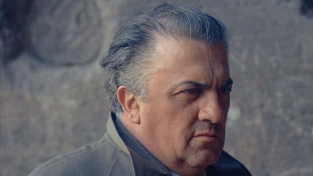 Federico Fellini im Porträt mit kritischem Blick.