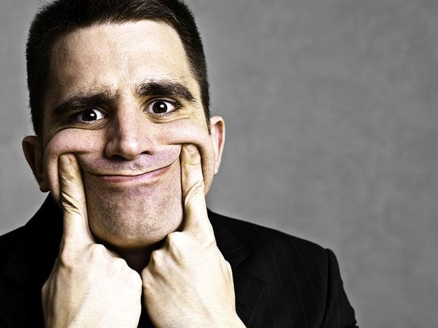 Ein Mann schiebt mit den Zeigefingern die Mundwinkel hoch und zwingt sich so zu einem Lächeln.