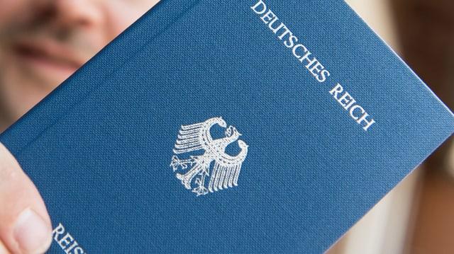 Eine Person hält einen erfundenen Reisepass mit der Aufschrift «Deutsches Reich» in der Hand.