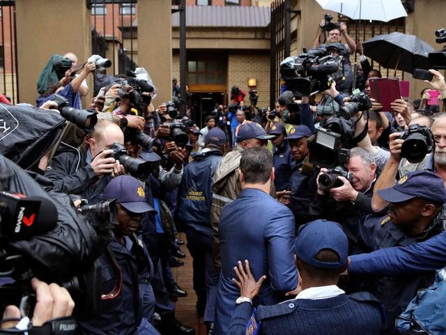 Medienandrang, in der Mitte geht ein Mann in blauem Anzug