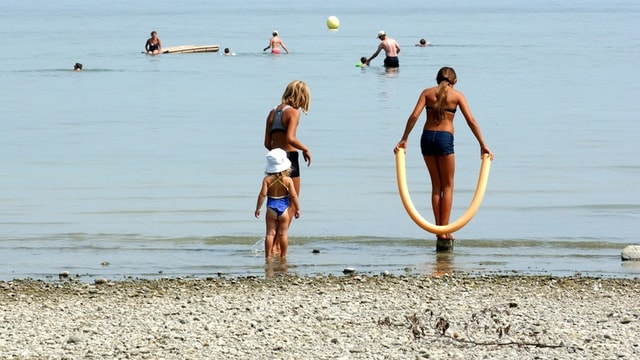 Kinder spielen am Seeufer.