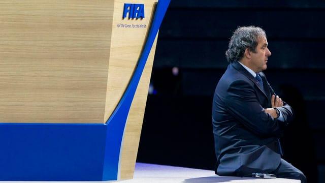 Michel Platini sitzt an einem Fifa-Anlass vor dem Logo des Weltfussballverbandes.