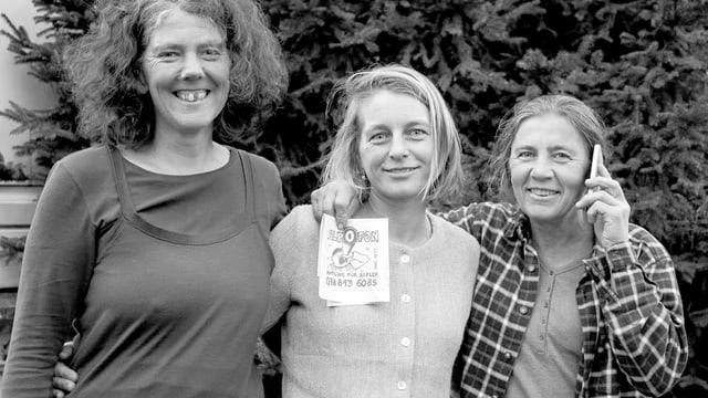 Drei Frauen lächeln, eine hält ein Smartphone ans Ohr.