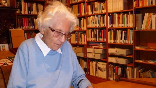 Marthe Gosteli sitzt an einem Tisch vor vielen Büchern, die die Schweizer Frauenbewegung dokumentieren.