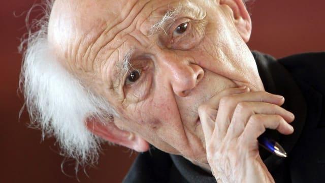 Ein Porträt von Sozialwissenschaftler Zygmunt Bauman, der seine Hand vor dem Mund hält.
