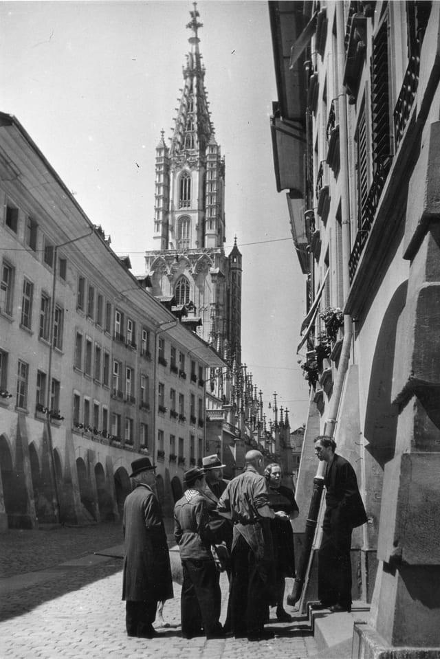Vier Männer und zwei Frauen stehen an einem Haus in einer Strasse in Bern. Im Hintergrund steht das Berner Münster.